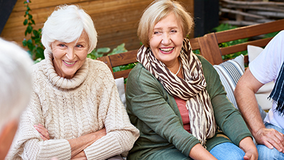 Pretty senior women with charming smiles listening to their male friend with interest while having gathering at cozy small patio